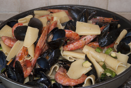 Traditional Italian sea dish:pasta with mussels prawns and zucchini