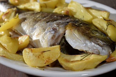 traditinal: traditinal  Italian sea dish: baked sea bream with potatoes Stock Photo
