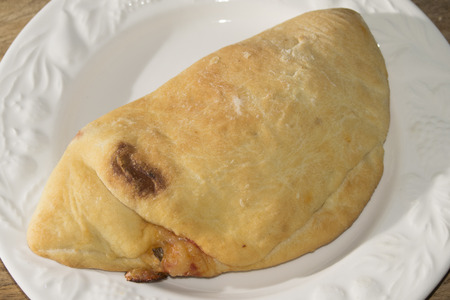leavening: typical neapolitan pizza roll with stuffed of tomato sauce and mozzarella