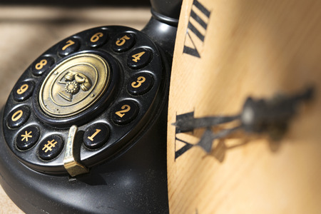 enumeration: clock with roman enumeration  and black antique phone with manual keys