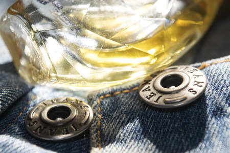 eau de perfume: abstract image for  concept of charm beauty and fashion with perfumes and button jeans
