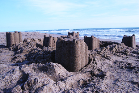 sandcastles: sandcastles on sea beach partly destroyed and at the dusk