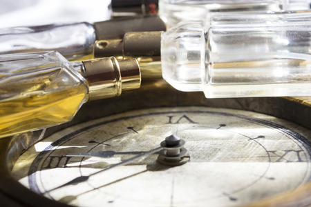 time passing: concept of time passing charm and beauty that wither through the image of a clock and some perfume bottles