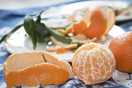 clementines: Two ripe clementines one peeled and one whole Stock Photo