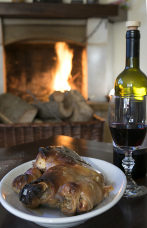porker: red wine goblet and roast piglet to eat  round the fireside