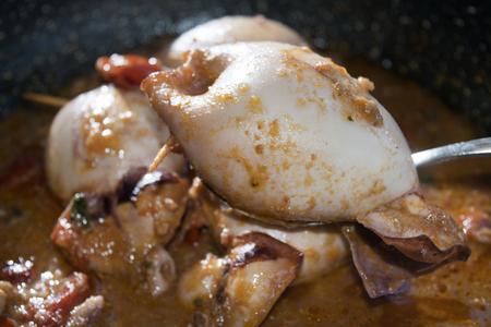 fish sauce: stuffed calamari with tomato sauce in saucepan Stock Photo