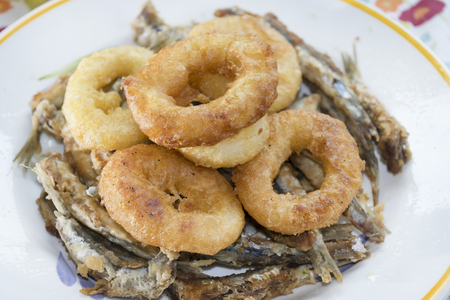 battered: battered and fried rings of squid anchovy fillets Stock Photo