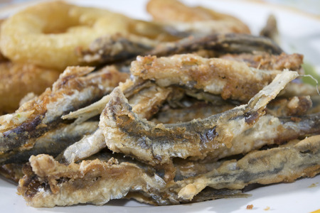 fish fry: fish fry with a dish of floured and fried anchovies