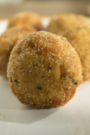 appetiser: fried sicilian arancina a traditional recipe of sicily made with rice with filling of mozzarella and ragout