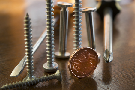 manual work: screws bolts and two cent  to symbolize the concept of manual work , professions and monetary   profits