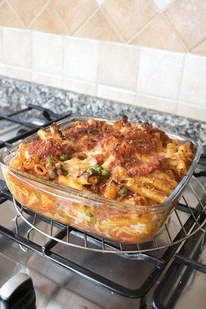 panful: meaty baked rigatoni withtasty filling  in an  oven pan of glass on a hob