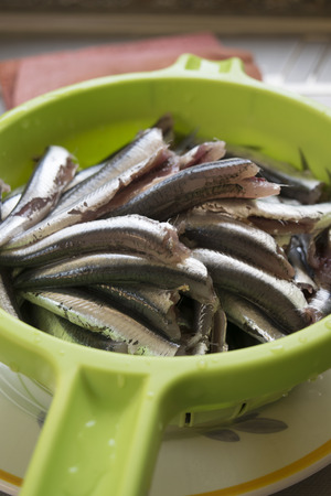 cleaned: raw anchovies just cleaned  in a green colander