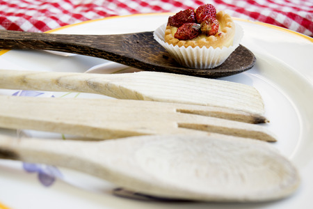 teacake: small cake at the strawberry on a wooden spoon