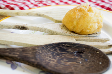 choux bun: chantilly  cream puff with icing sugare on wooden spoon