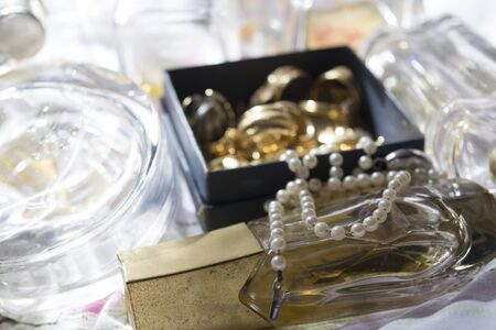 captivation: old and precious pearl necklace on a perfume bottle with gold family jewels