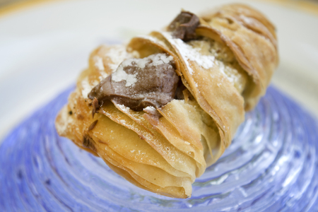 choux bun: crispy neapolitan sfogliatella with icing sugar and filled with melted chocolate and Stock Photo