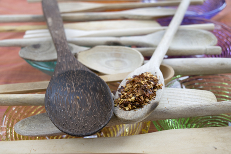 crushed red peppers: crushed red peppers on a wooden spoon with nearby others wooden spoons arranged in row