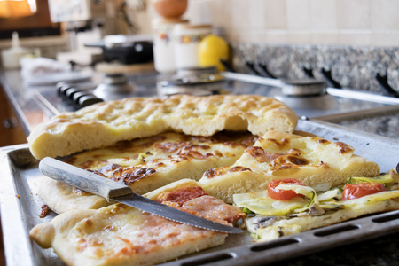hob: assortment of scraps of pizza in a baking tray on a hob Stock Photo