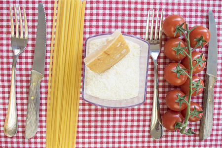 disposed: flat lay of pasta at tomato with  raw spaghett icherry tomatoes and parmesan between cutleries