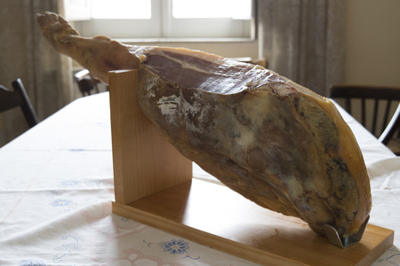 proper: whole raw spanish ham on the proper cutting board Stock Photo