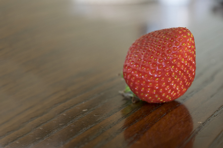 overripe: overripe organic strawberry on a wooden table