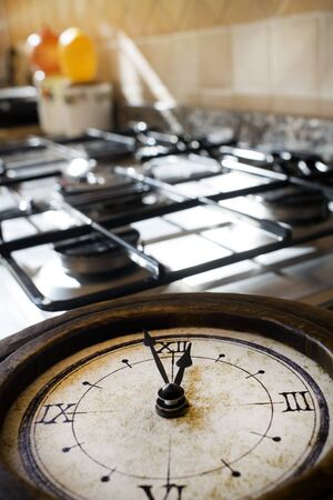 stovetop: concept of lunch time with an old skeleton clock on a stove-top