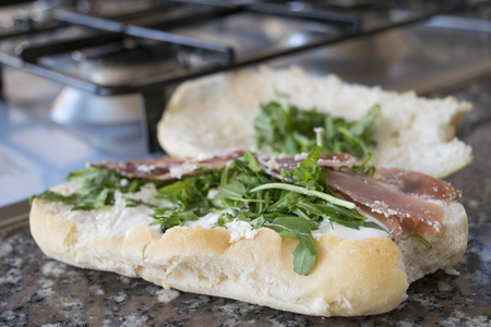 sanwich: bread roll filled with arugula bresaola and parmesan cheese