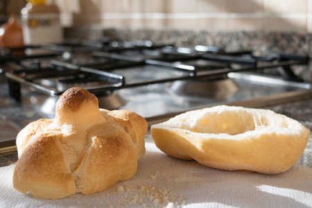 half  cut: bread roll half cut with on a stove-top Stock Photo