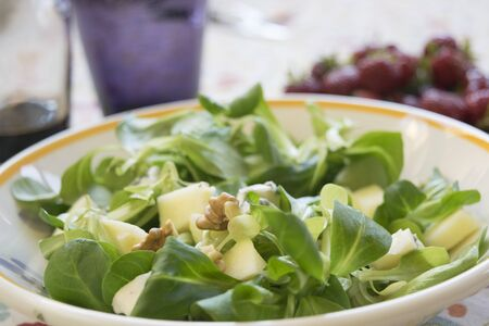 valerian: valerian salad with walnuts in a white dish