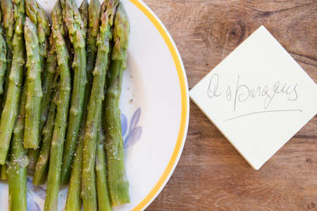 bunch of steamed asparagus with the writing on the post-it Stock Photo