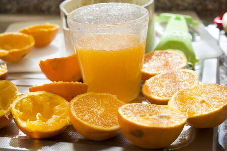 juice squeezer: fresh-squeezed orange juice in a glass with citrus-fruit squeezer