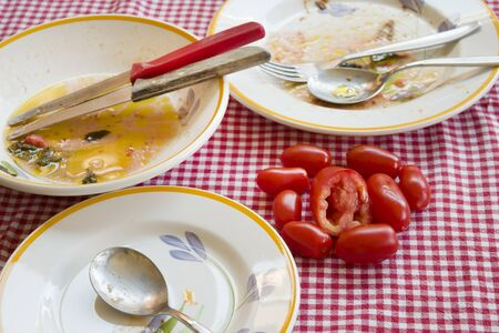 piccadilly: fresh piccadilly tomatoes on a table with dirty plates Stock Photo