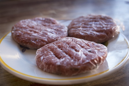 frozen meat hamburger wrapped in plastic film Stock Photo