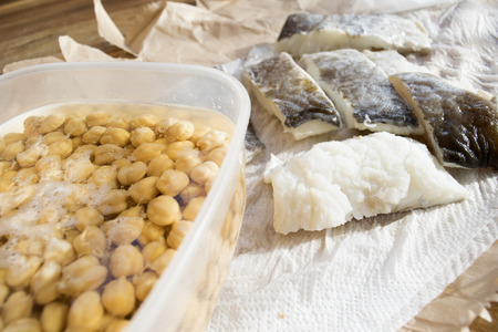 raw fillets of salted codfish with chickpeas in soaking Stock Photo