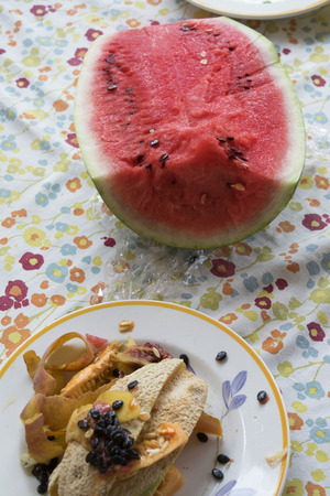 leftovers: watermelon and leftovers after the lunch on a set table Stock Photo