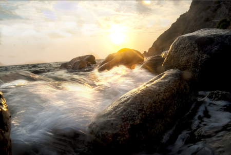 crepuscle: sea sprays on a cliff at the sunset