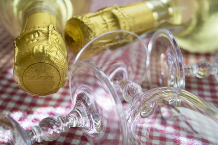 detail of the neck of a champagne bottle surrounded from crystal glasses Stock Photo