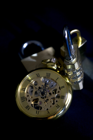 time and security with an old clock and some padlocks Stock Photo