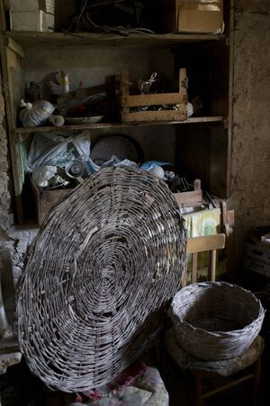wicker basket on a old chairs in a basement with walls in tuff Фото со стока