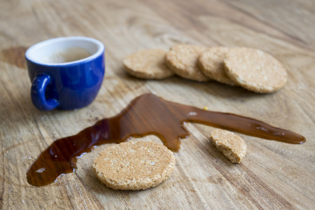 galletas integrales: cup of espresso coffee spilled on a wooden table near wholemeal biscuits