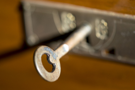 old brass key in a keyhole of a wooden drawer