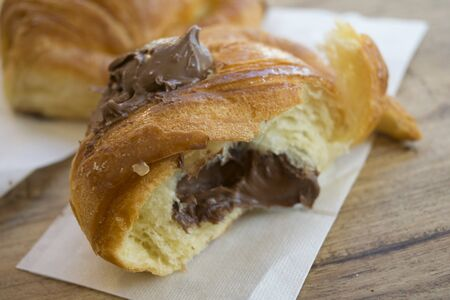 chocolate croissant half cut stuffed with melted chocolate