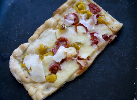 piece of pizza with cherry tomatoes and parmesan cheese