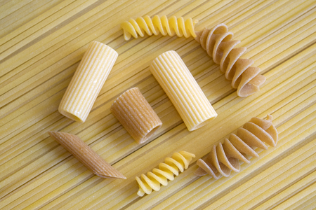 variety of normal and whole meal pasta on a spaghetti background