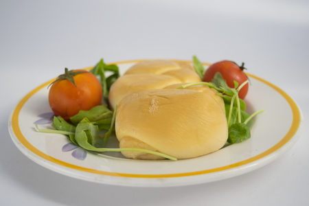 Scamorza cheese on a wooden dish with cherry tomatoes and lettuce Stock Photo