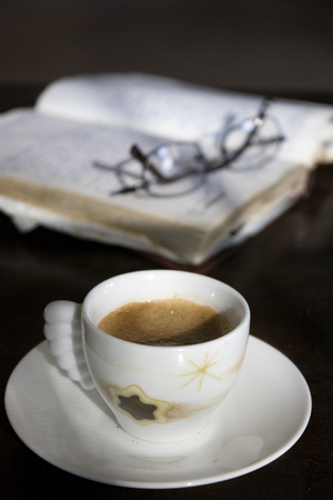 cup of espresso coffee and old diary in dim light atmosphere