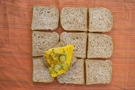 composition of slices of sandwich bread with a slice of zucchini omelette