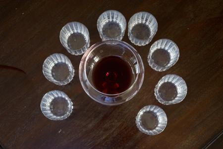 Ballon de cristal avec une dispersion de vin rouge avec près de petits verres tintement Banque d'images - 94068470
