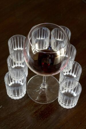 crystal balloon with a degustation of red wine with near small wisky glasses