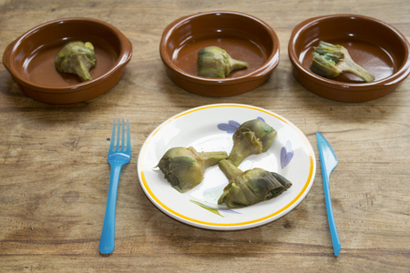 stewed heart artichokes cut in segments in a series of pottery dishes